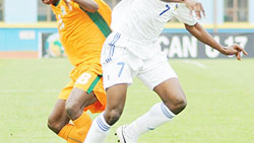 Charles Tibingana (R) fights for the ball with an Ivory Coast player during the 2011 Africa Junior Championship. The New Times/File.