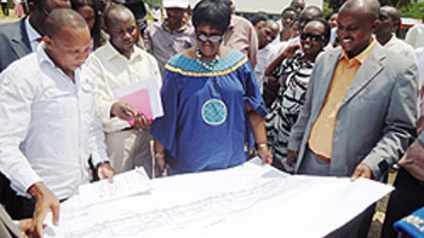 Dr Agnes Binagwaho (C) examines the proposed master plan of the new hospital to be built in Karongi beginning next month. The New Times Sam Nkurunziza