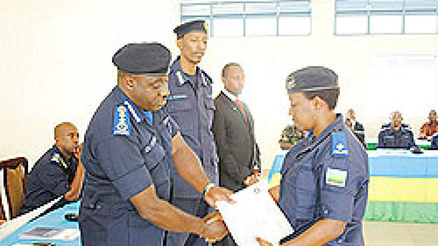 Police Chief, Emmanuel Gasana hands over a certificate to one of the trainees as the head of CID, Christophe Bizimungu looks on NewTimes/Courtesy.