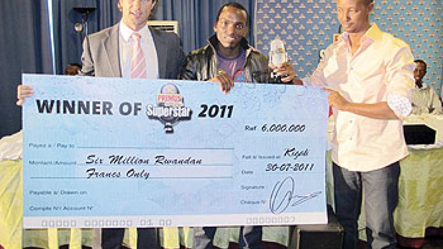 (L-R) Sven Piederiet, MD of Bralirwa and Joseph Mushoma, CEO of EAP present the cheque prize of Rwf6million to the Primus Superstar Tom Close.
