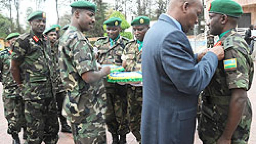 General Sekuba Konate decorates Col. Sam Baguma as Chief of Defence Staff Lt. Gen. Charles Kayonga (C) and the Chief of staff of the Reserve Force Lt. Gen Fred Ibingira look on yesterday. The New Times/John Mbanda