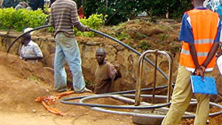 Workers lay fibre optic cables. The infrastructure will help bring down costs. The New Times /File