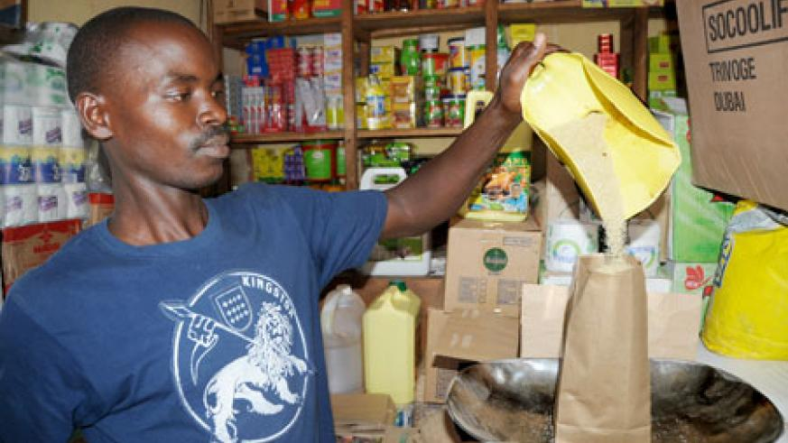 A shop attendant packages sugar at Kigali's Kimironko market yesterday. The price of the commodity has gone down after government's intervention. The New Times/John Mbanda