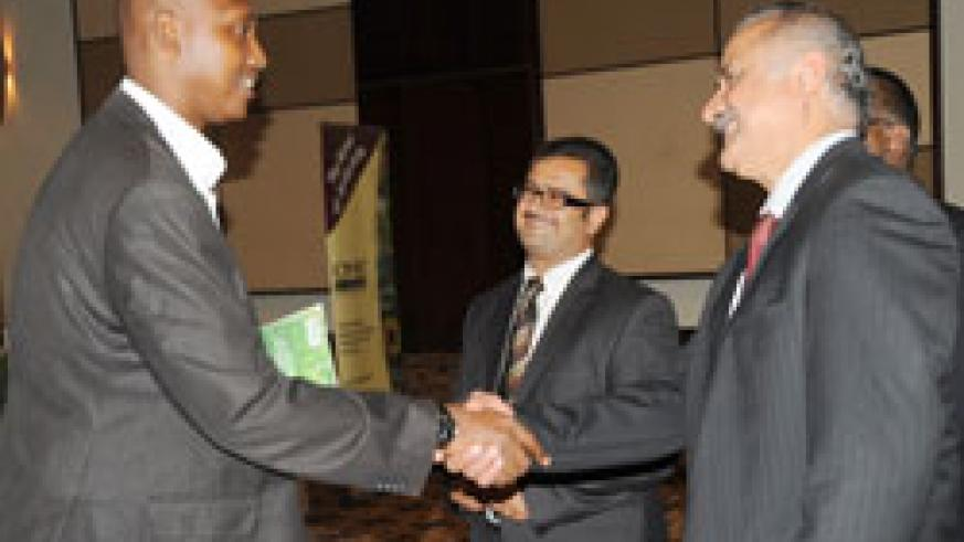 MINAGRI PS Ernest Ruzindaza (L) greets Yasir Syed, the Director of Biofert as Eagle Eye Africa Director Imran Morani looks on during the launch of the eco-friendly fertilizers, in Kigali, yesterday. The New Times /John Mbanda.