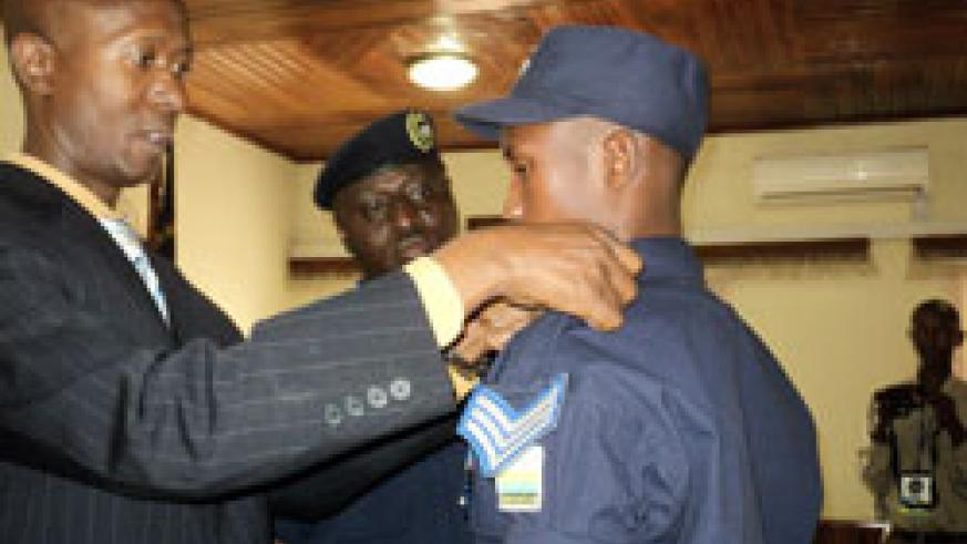 Minister of Internal Security,Musa  Fazil Harerimana,  decorates Frank Bizimungu with the rank of Sergeant as the IGP Gasana looks on. The New Times /Courtesy.