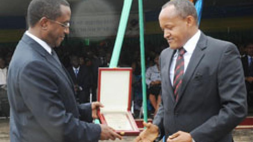 Senate President Vincent Biruta (L) awards the Chairman of the PSF Faustin Mbundu on tax payers' day last week. A new system will enhance tax collection The New Times /John Mbanda.