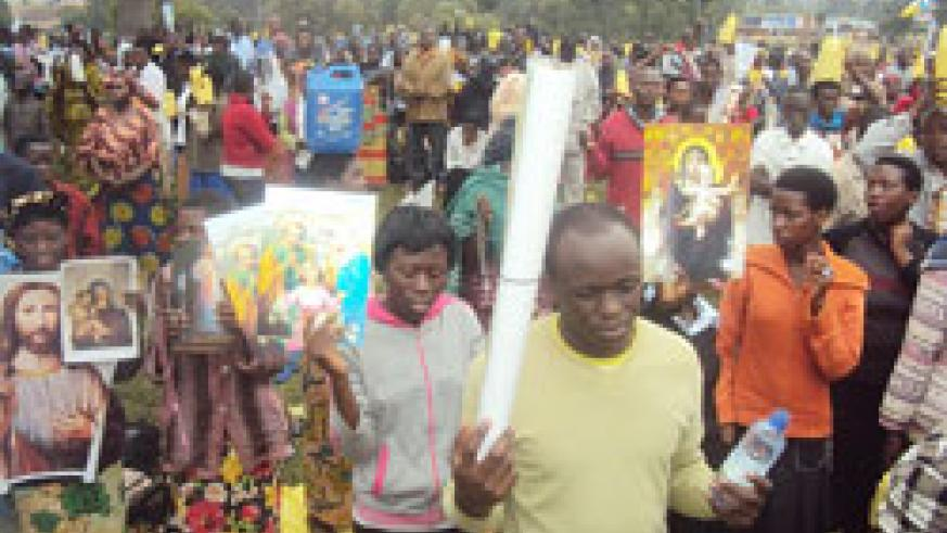 Thousands of Catholic faithful held placards with images of the Virgin Mary as they trekked to Kibeho to celebrate the Assumption Day. The New Times /Daniel Sabiiti.