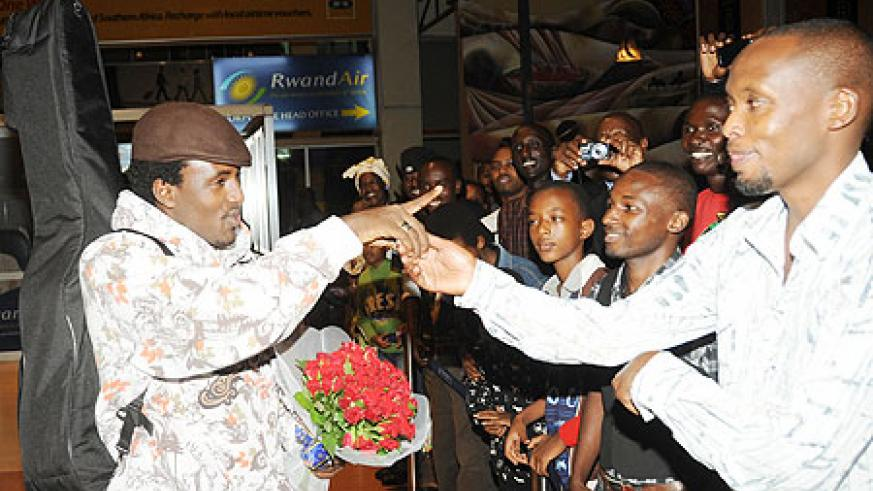 Alpha Rwirangira greets fans at Kigali International airport yesterday. The New Times John Mbanda)