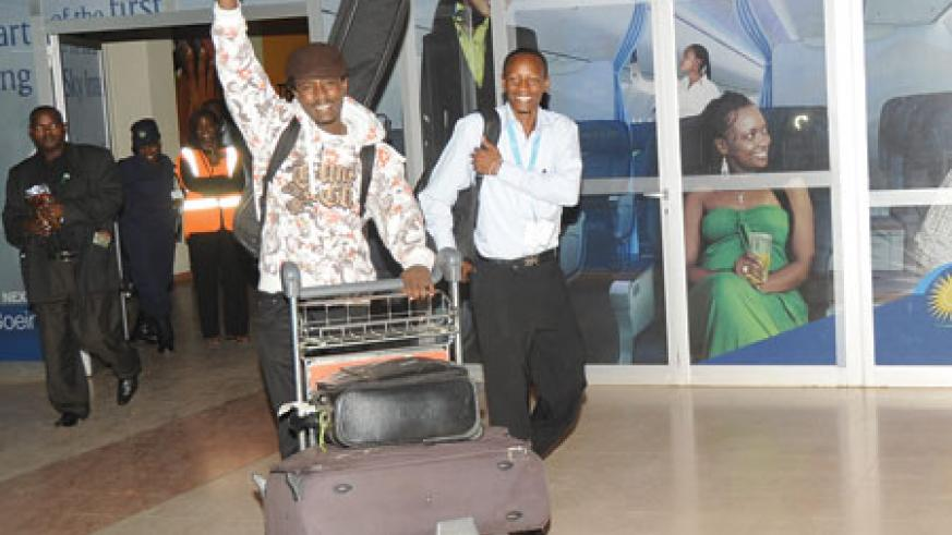 I AM THE CHAMPION! Alpha emerges from the arrivals terminal of the Kigali International Airport.