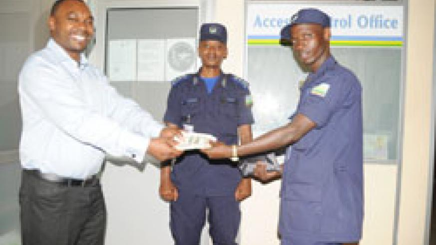 Tanzanian citizen, Rajab Furaj Juma (L), receiving his US$19,700 from police constable Willy Bizimana (R) who picked the money as CSP Felly Bahizi (C) looks on