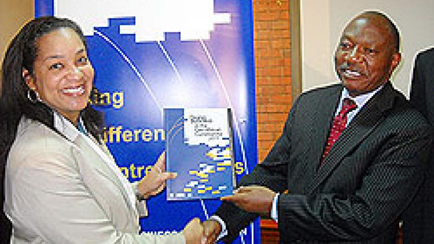 World Bank Operations Office,r Maria Miller, hands over a copy of the 2011 Doing Business in the EAC Report to the EAC Deputy SG in Charge of Planning, Dr. Enos Bukuku. The New Times /Courtesy