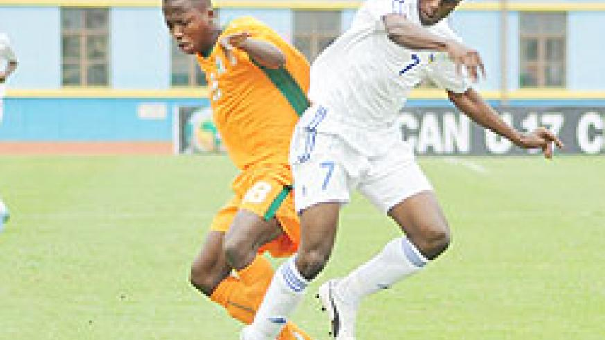 Charles Tibingana (R) fights for the ball with an Ivory Coast player during the 2011 Africa Junior Championship. The New Times/File Photo