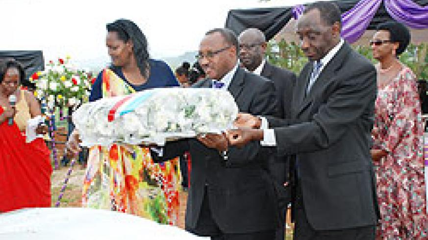 Minister in charge of Cabinet affairs Protais Musoni (C) and MP Kayinamura  (R) lay a wreath on the casket of Mzee Haajje Gashegu. The New Times/ Stella Teta.