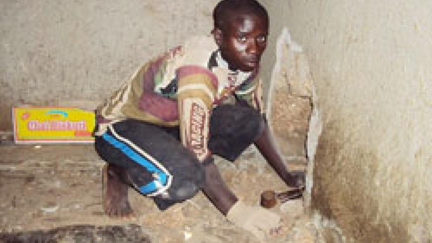 CAUGHT RED-HANDED; Adalbert Mutabazi demonstrates how he drilled through a wall to rob a barber-shop in Gitarama. Photo New Times /Daniel Sabiiti