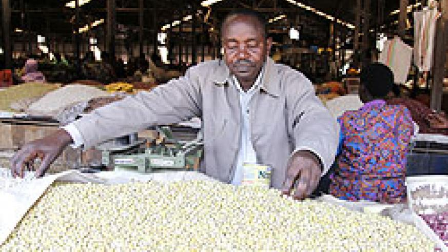 Augustin Musoni a researcher from RAB and bean breeder inspects beans at Kimironko market The New Times /Timothy Kisambira