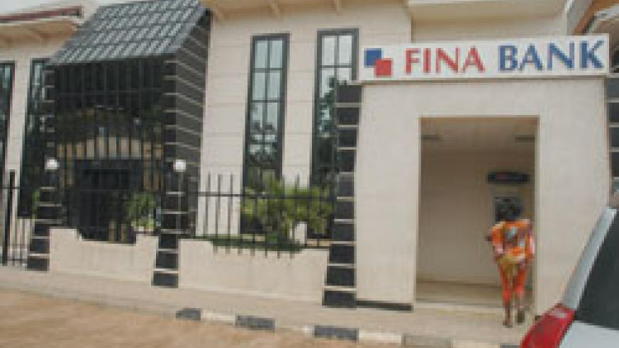 A FINA Bank customer accessing the bank's ATM machine. The New Times / File