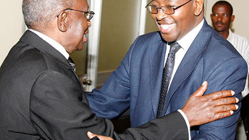 Prof. Peter Rwanyindo Ruzirabwoba of local think tank IRPD (L), welcomes Local Government Minister, James Musoni,  to the meeting yesterday. The New Times /Timothy Kisambira