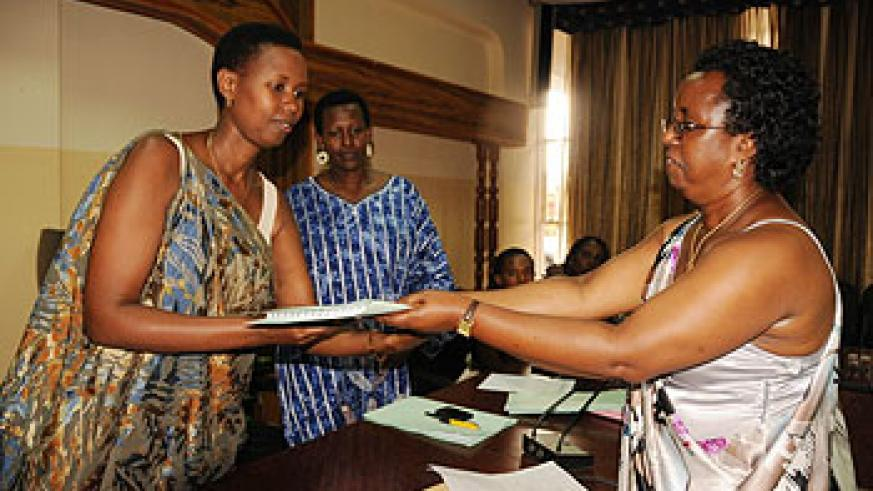 Berrancila Nyinawankusi hands over instruments of power to her successor Alice Ababo as vice Mayor Hope Tumukunde looks on. The New Times /Courtsey Photo