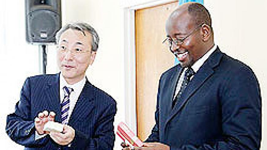 Local Gov't Minister, James Musoni,(R) admires a gift from Kim Won Jin, from the Korean Ministry of Public Administration and Security yesterday. The New Times/ Timothy Kisambira