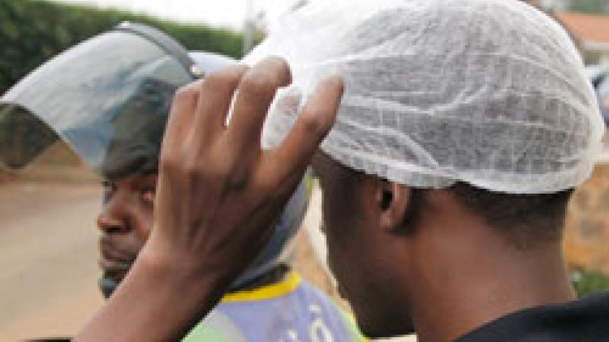 A Taxi-moto passenger tries on the smart cover head. The NewTimes /Timothy Kisambira