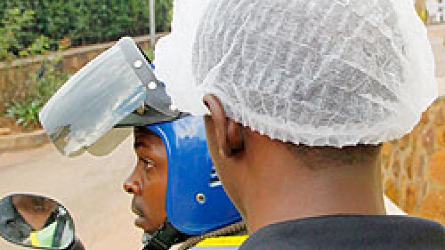 Controversy is brewing over who should meet the cost of the smart cover headgear offered to passengers using taxi-motos. The New Times/ File photo