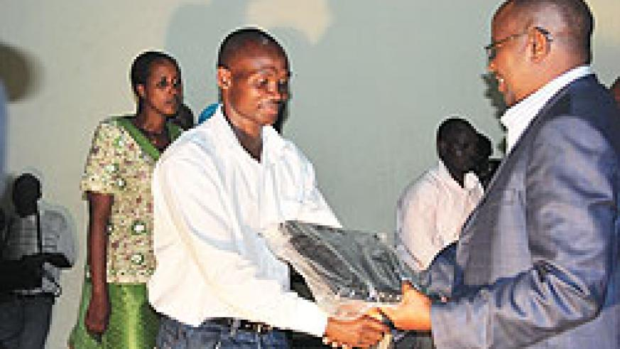 The Minister of Local Government James Musoni hands over a laptop to a local leader. The government wants grassroots leaders to use computers. The New Times / file photo