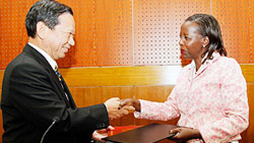 The Japanese Ambassador to Rwanda Kunio Hatanaka (L), exchanges documents with Foreign Affairs Minister Louise Mushikiwabo after signing a grant yesterday.The New Times /Timothy Kisambira.