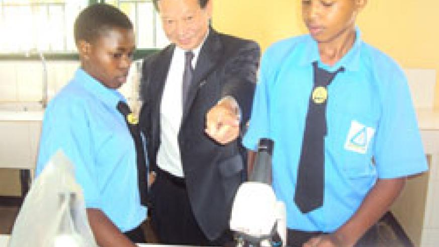 Japanese envoy to Rwanda Kunio Hatanaka engages students in laboratory tests during the commissioning of eight new classrooms at Kayonza Modern School The New Times /Stephen Rwembeho.