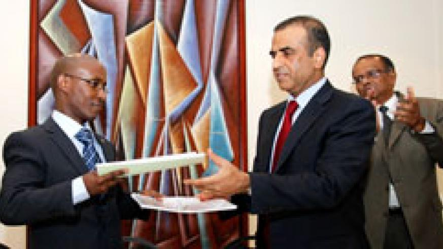 ICT Minister, Ignace Gatare, (L) exchanges documents with Sunil Bharti Mittal, chairman and director of Bharti Artel. The New Times /Timothy Kisambira