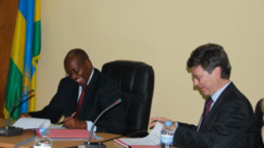 Prof Jeffrey Sachs (R), the Director of Earth Institute and Minister Musoni of Local Government sign the partnership agreements in Kigali on Thursday. The New Times /Courtesy.