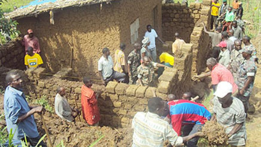 RDF personnel join residents to put up houses for vulnerable residents. The New Times /File