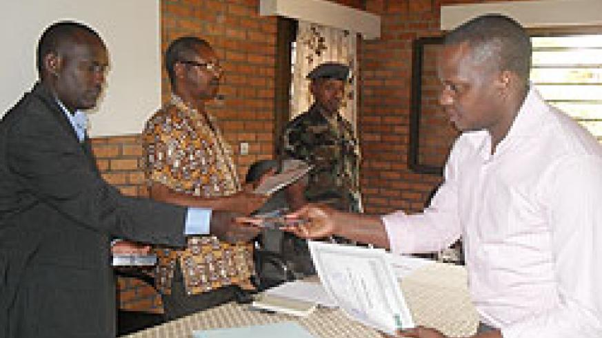 L-R-Dr Gaspard Rwanyiziri the CGIS Director, Vice Rector of NUR, Prof Musahara Herman and Lt Col Emmanuel Gashayija of the RDF Airforce Unit hands over a certificate to a participant. The New Time /Courtesy