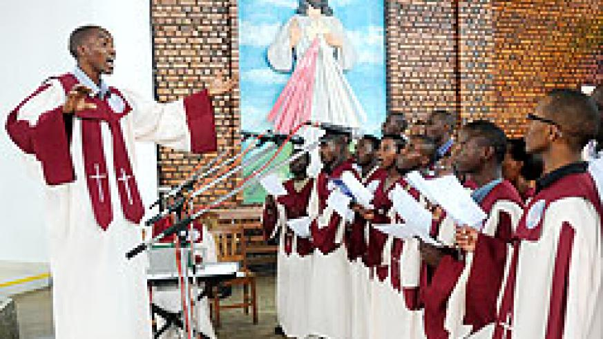 The choirmaster leads members and other worshippers to sing at Remera-based Regina Pacis during a memorial service of the US 9-11 victims yesterday.  The New Times/ John Mbanda