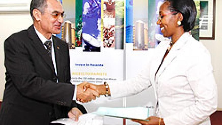 State Minister Eng. Coletha Ruhamya (R) and Mohamed Safeyeldin from ORASCOM exchange documents after the signing ceremony yesterday. The New Times /Timothy Kisambira