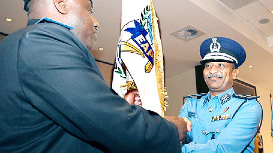Sudan's Gen. Hashim Osman Ali Hussein handing over EAPCCO's flag to his successor, IGP Emmanuel Gasana. The New Times/ Timothy Kisambira