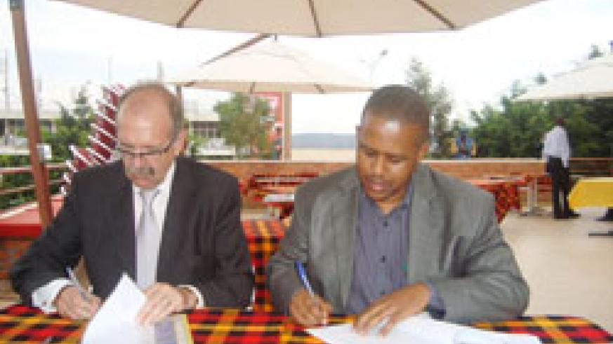 WDA's Jerome Gasana and SHair Academy's Nigel McCarthy sign the agreement to institute a hair dressing academy in Rwanda. The New Times /courtesy.
