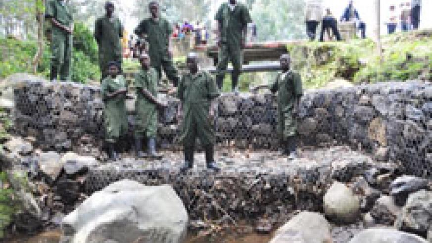 Veterans stand near one of the gabions constructed along Rwebeya water stream.The New Times / B Mukombozi