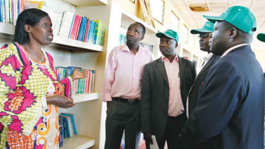 Irene Munimpundu (L), a librarian at Lycee de Kigali shows around some of the school's Old Boys including Christopher Bazivamo (R) and Augustine Mutijima(2R), both members of the newly formed alumni committee, yesterday. The New Times/Timothy Kisambira.