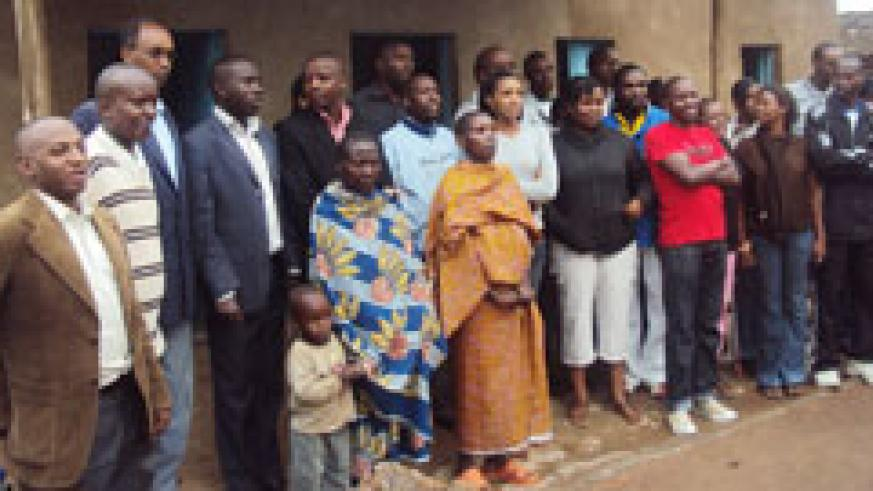 Some Huye district  officials pose for a group photo with the beneficiaries of the houses. The New Times /JP Bucyensenge.