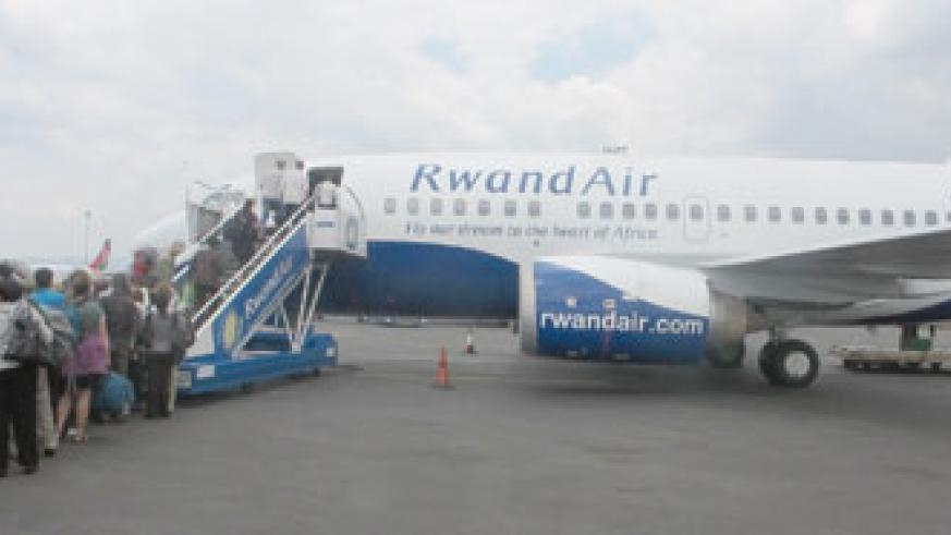 Passengers embark on a Rwandair plane at the Kigali Airport. The national carrier has upped its services. The New Times /File.