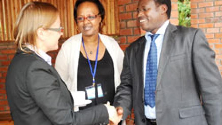 The Permanent Secretary in the Ministry of Health,  Dr. Uzziel Ndagijimana (R) talks to Christel Vermeersch from World Bank as Yvonne Kayiteshonga, in charge of mental health at MoH, looks on during the meeting to assess the impact of Performance Based Fi