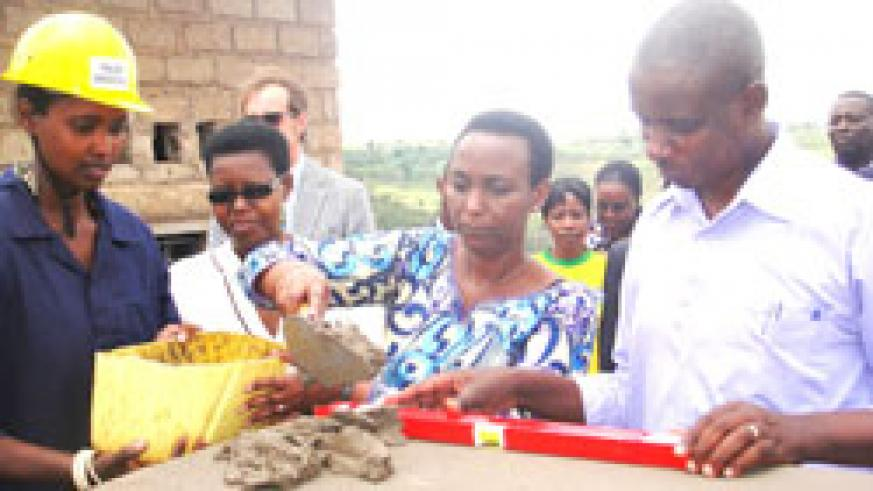 Gender Minister Aloysia Inymba lays a foundation stone for the construction of the Women Opportunity Centre in Kayonza as mayor John Mugabo (R) looks on. The New Times  / S Rwembeho