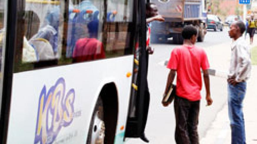 Commuters at a Kigali bus stop. Commuters have raised concerns  insufficient bus stops on some routes which compel them to walk long distances. New Times /Timothy Kisambira