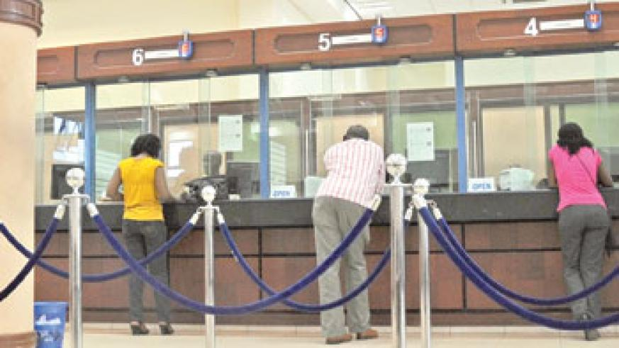 Despite central bank's implementation of modern payment systemes long queus are still visible within banks. The New Times / File