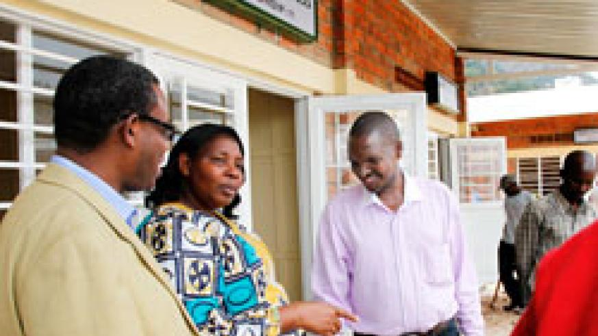 Mayor Solange Mukasonga, (C) talks to Francois Nsengiyumva(L) of Atraco and  Charles Ngarambe (R) the Chairman of the Transporters' association on her arrival at the new offices of OMEGA Express one of the upcountry bus operators. The New Times/Timothy Ki