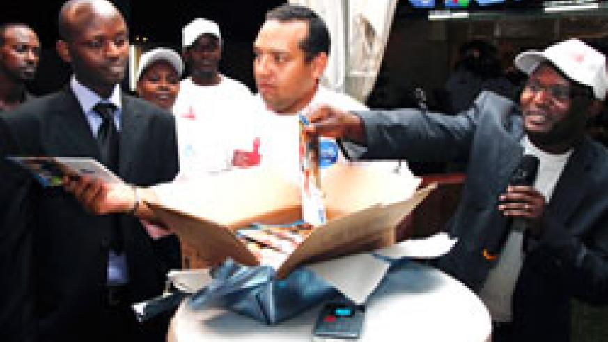 SWAHAP East Africa Region Coordinator, Daniel Mwaura, (R) together with Tigo's acting CEO, Diego Camberos, and (L) distribute HIV Booklets. The New Times Timothy Kisambira