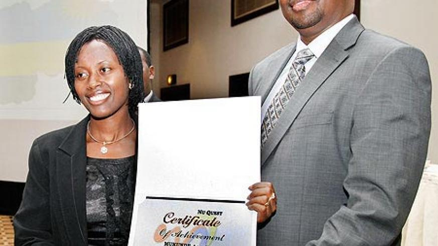 James Musoni (R)  hands a certificate to Kicukiro District Vice Mayor Angelique Mukunde after the completion of the leadership course.The New Times /Timothy Kisambira