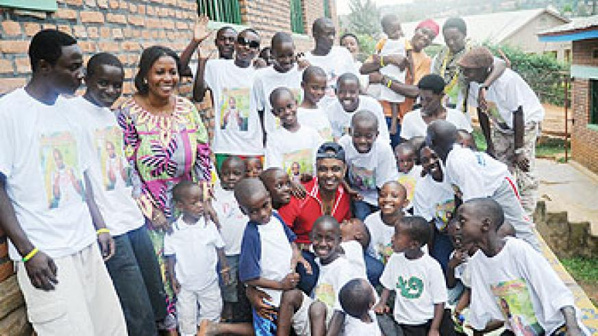 Scooper Knight (clad in red shirt) poses for a group photo with Mpore PEFA orphans. The New Times/John Mbanda.