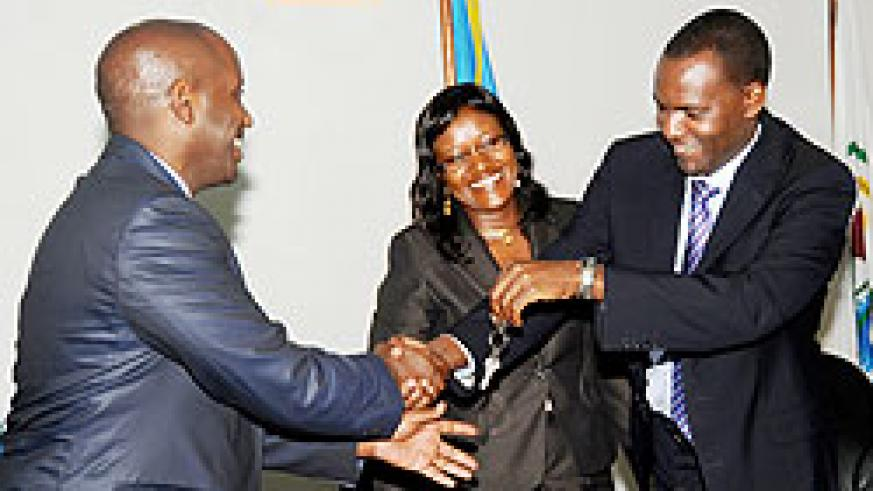 Outgoing Permanent Secretary in the Ministry of EAC Robert Ssali (R) hands over office keys to the new Permanent Secretary, William Kayonga (L) as EAC Minister Monique Mukaruliza looks on. The New Times\John Mbanda.