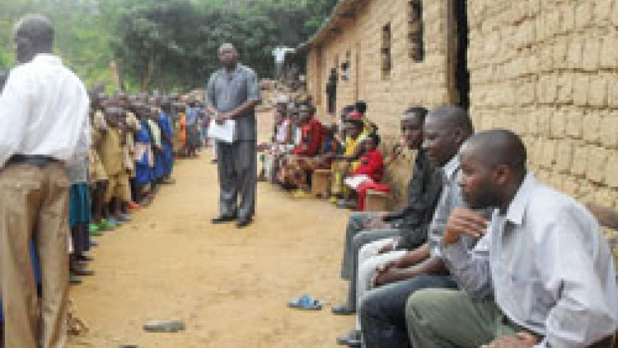Felix Ugrimbabazi (R) seated with some parents as the Ecole Primaire Busake headmaster Malachie Birege addresses pupils in front of their classrooms. The New Times  / Grace Mugoya